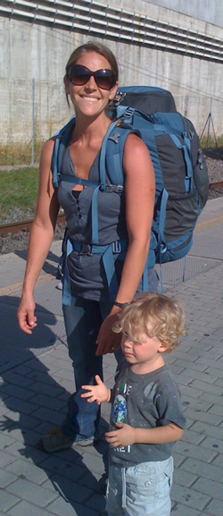 Jill, waiting with Rummy for a train. REI travel pack on her back.